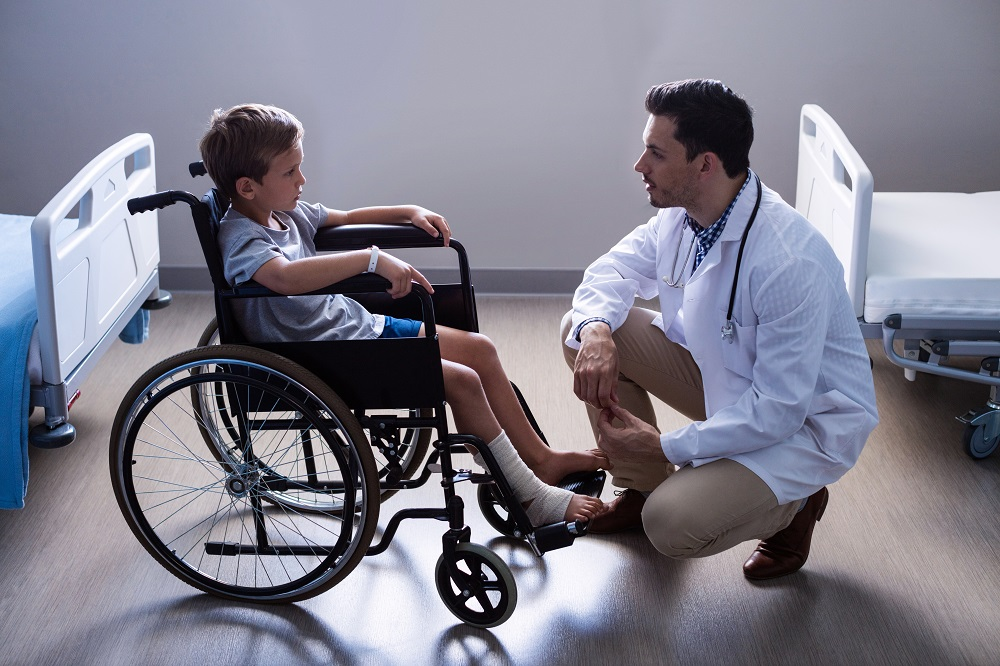 Boy in wheelchair talking to doctor