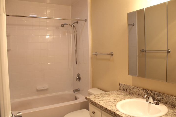 The bathroom has been updated with a new, granite countertop and a  new cabinet.