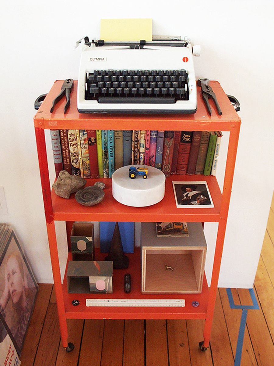 A typewriter, books, Matchbox tractor and other objects on an orange utility cart.