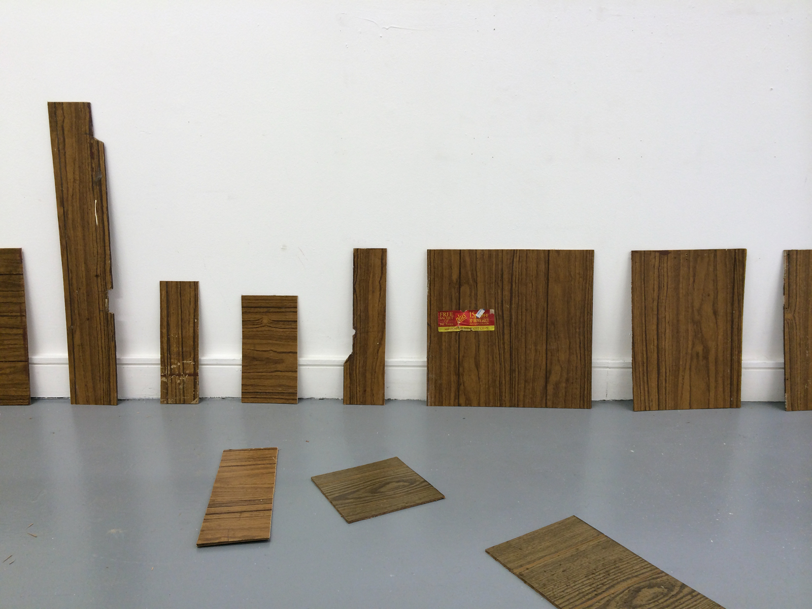 11 wood panel pieces of various shapes leaning against a wall and on the floor.