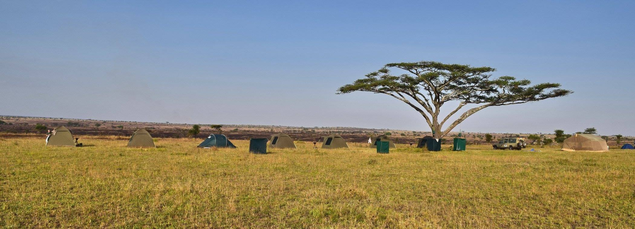 """Mobile Safari (Different than a permanent tent camp experience) -- with  """"short drop"""" toilets and portable hot water shower arrangements."""