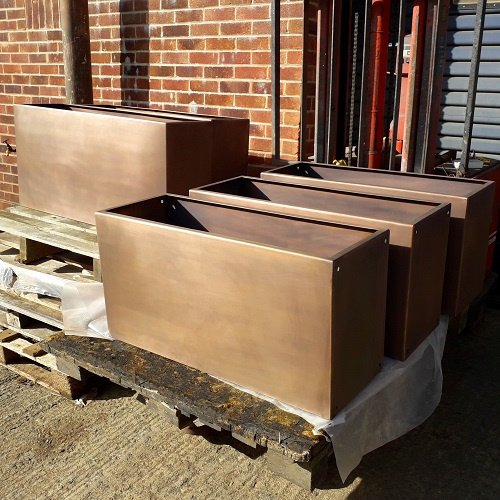 Thermal metal coating bronze finish AM.7 on garden planters.