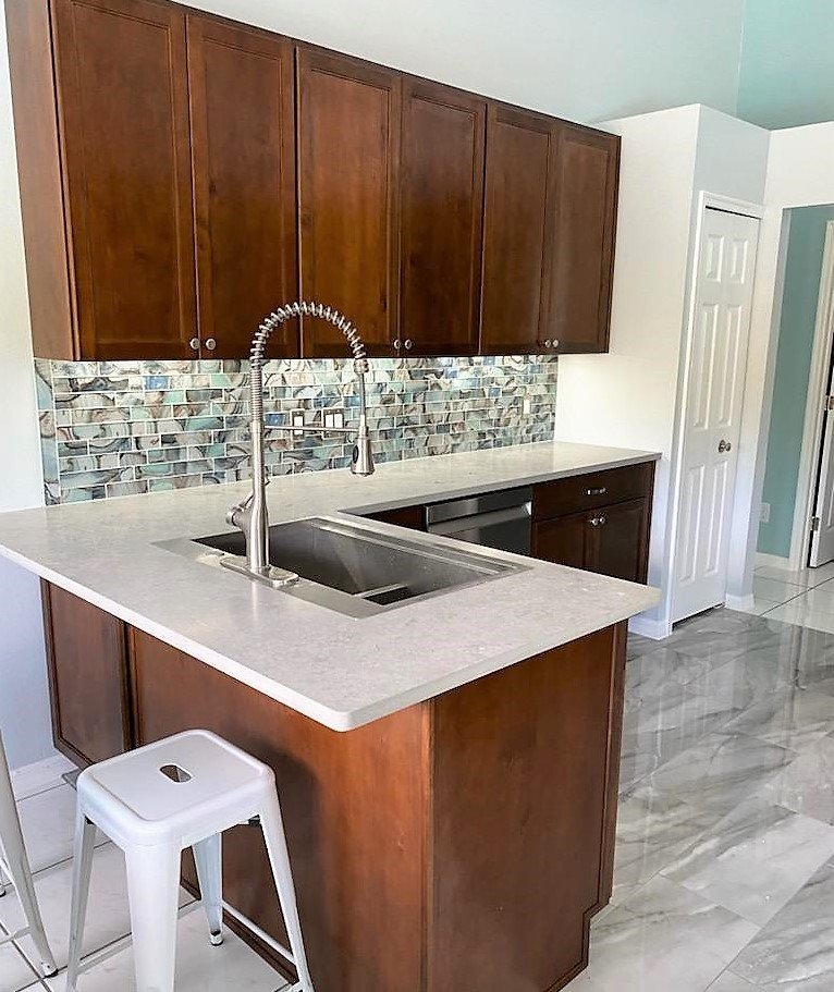Beautiful kitchen showcasing a big sink, quartz countertops, and overhang.