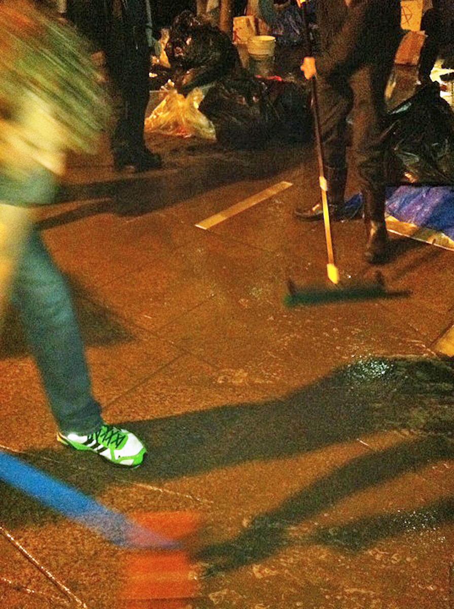 Two men scrub at a wet paved area with brooms, at night in orange streetlight.