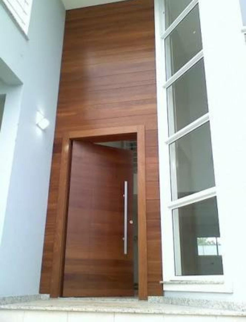 Porta de entrada pivotante, mais painel de madeira.