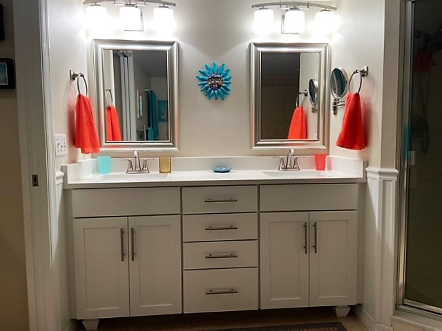 Timeless white clean vanity featuring double sinks and mirrors with brush nickel hardware.