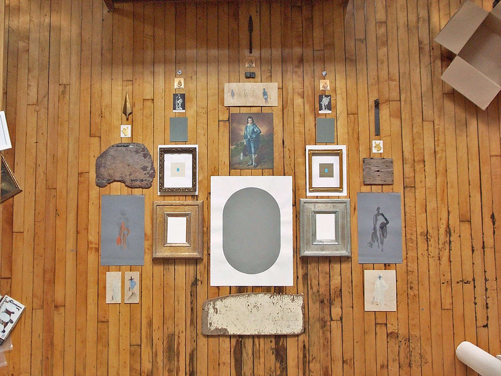 View from above of paintings, drawings and objects arranged on a wood floor.
