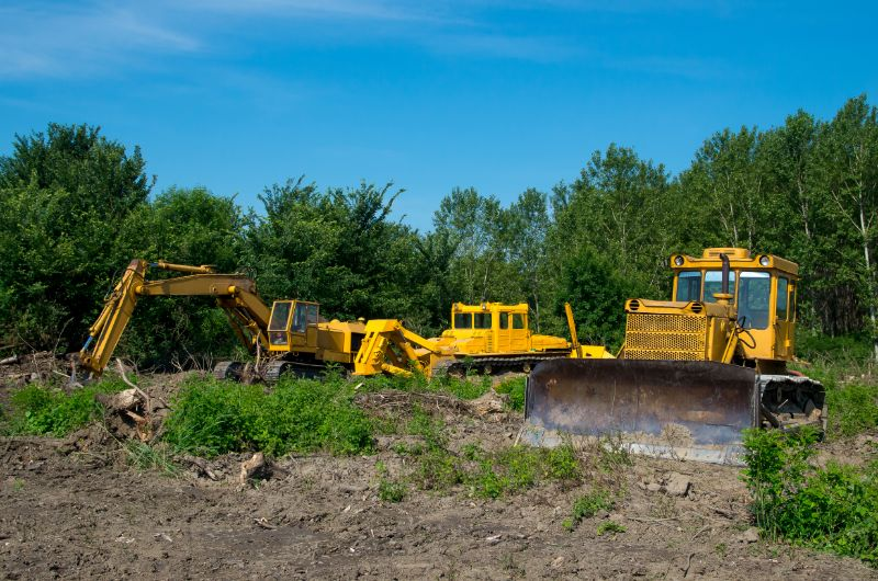 Excavator and bulldozer clearing forest land