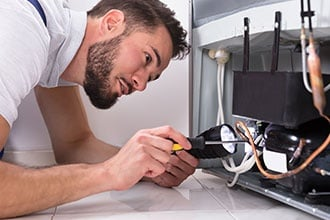 Technician Repairing Refrigerator