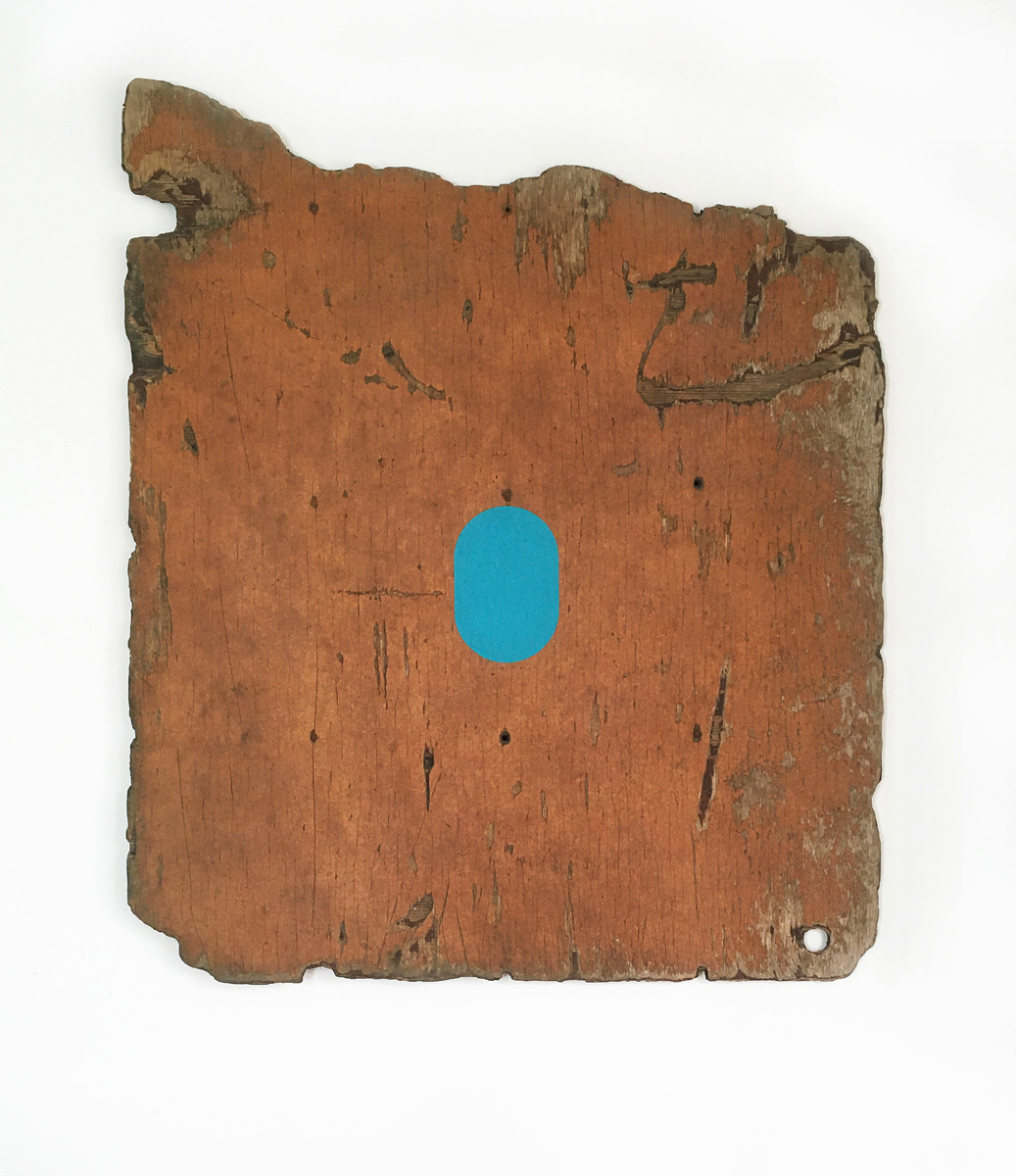 A large piece of distressed painted plywood with a turquoise oval in the center.