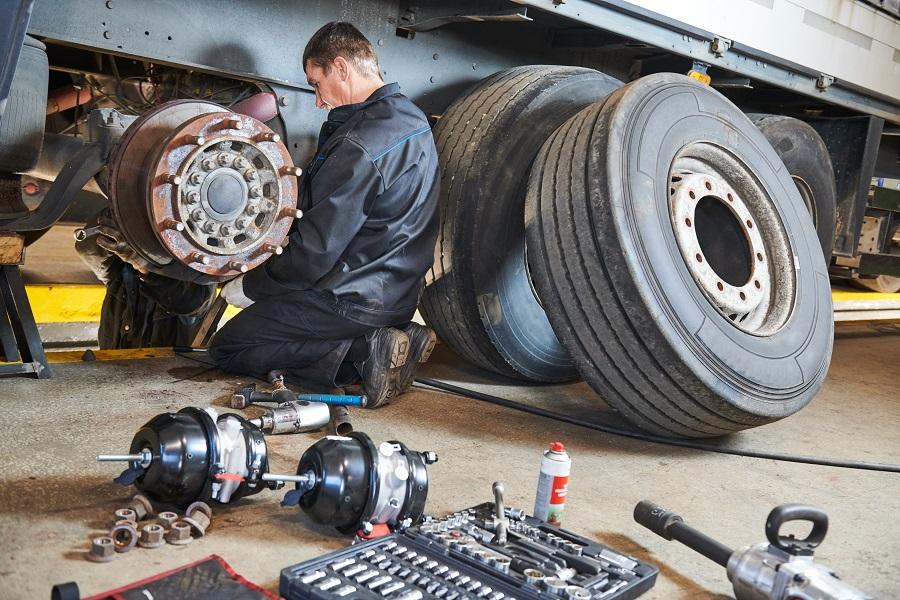 Car Repairman Fixing Truck Tire