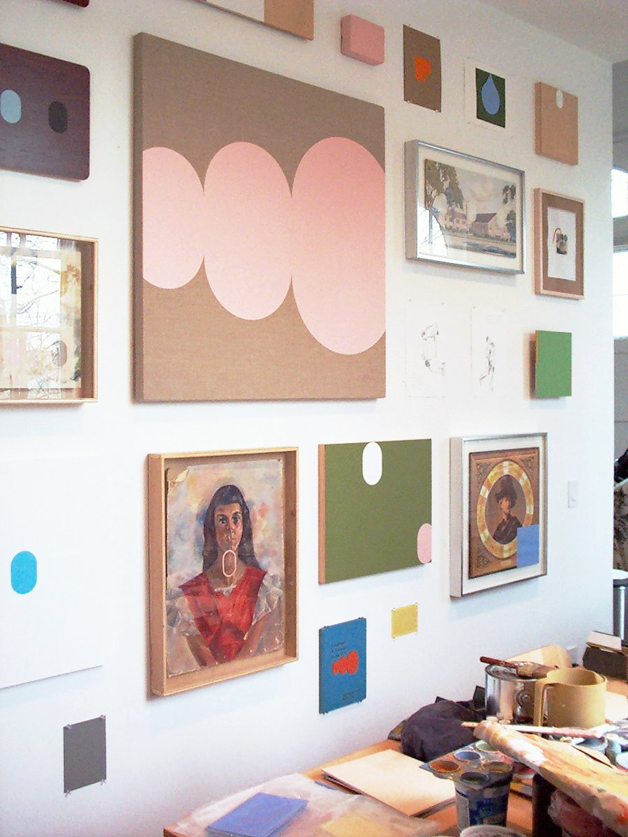 Colorful modern paintings and drawings on a wall behind an artist's worktable.
