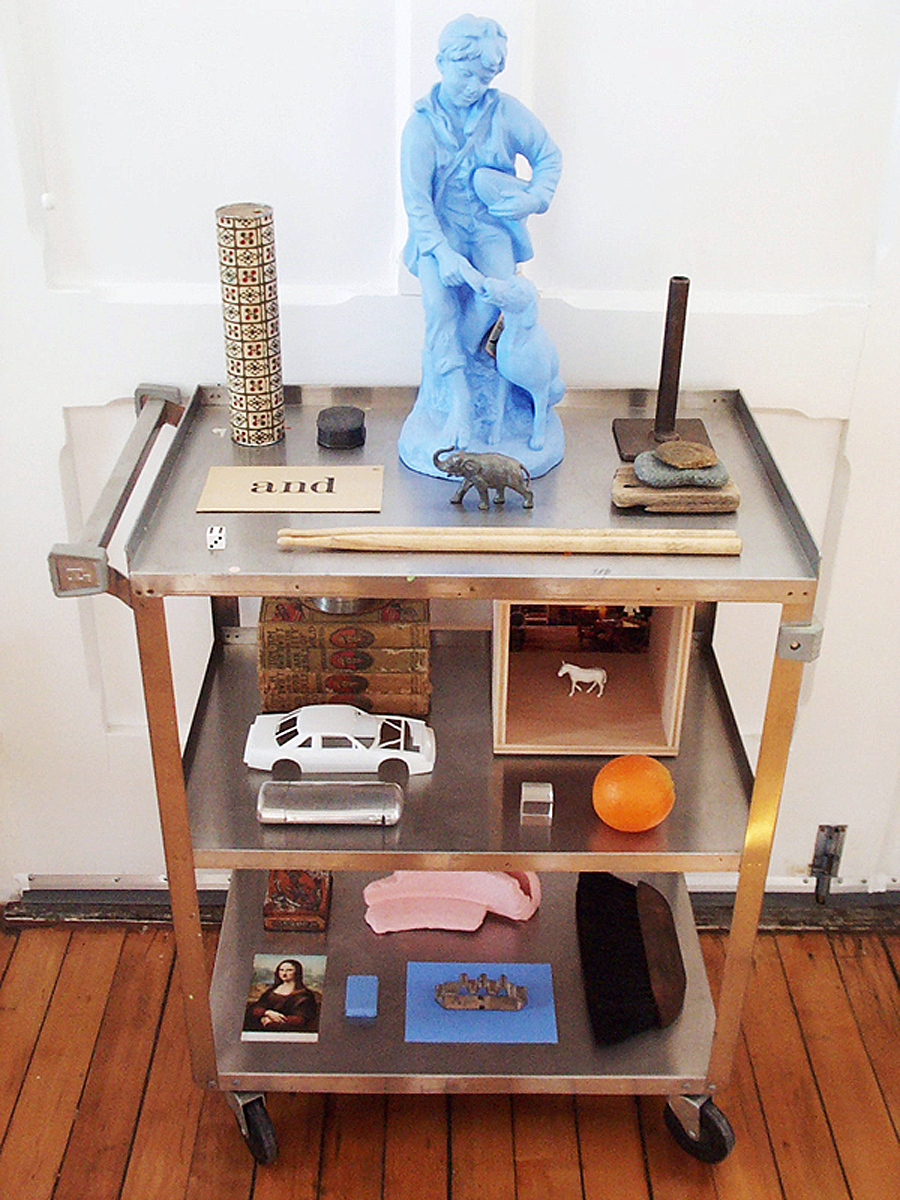 A utility cart with objects on it, including a blue painted statue of a boy and dog.
