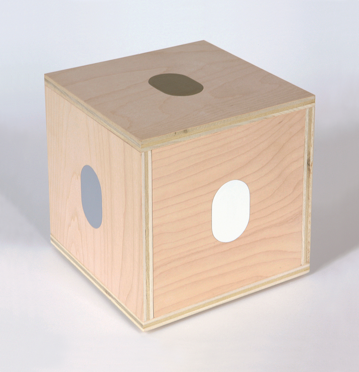 A plywood cube with gold, grey and white ovals painted on the top and sides.