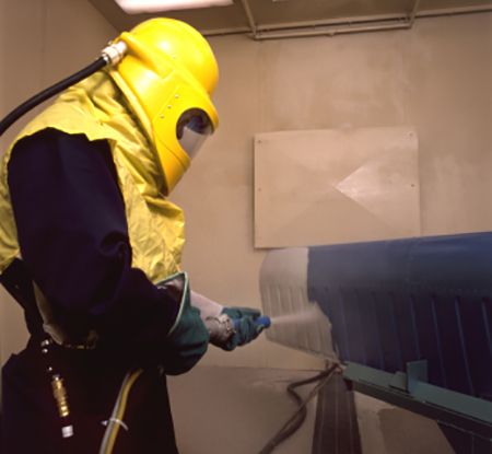 Worker sandblasting air duct