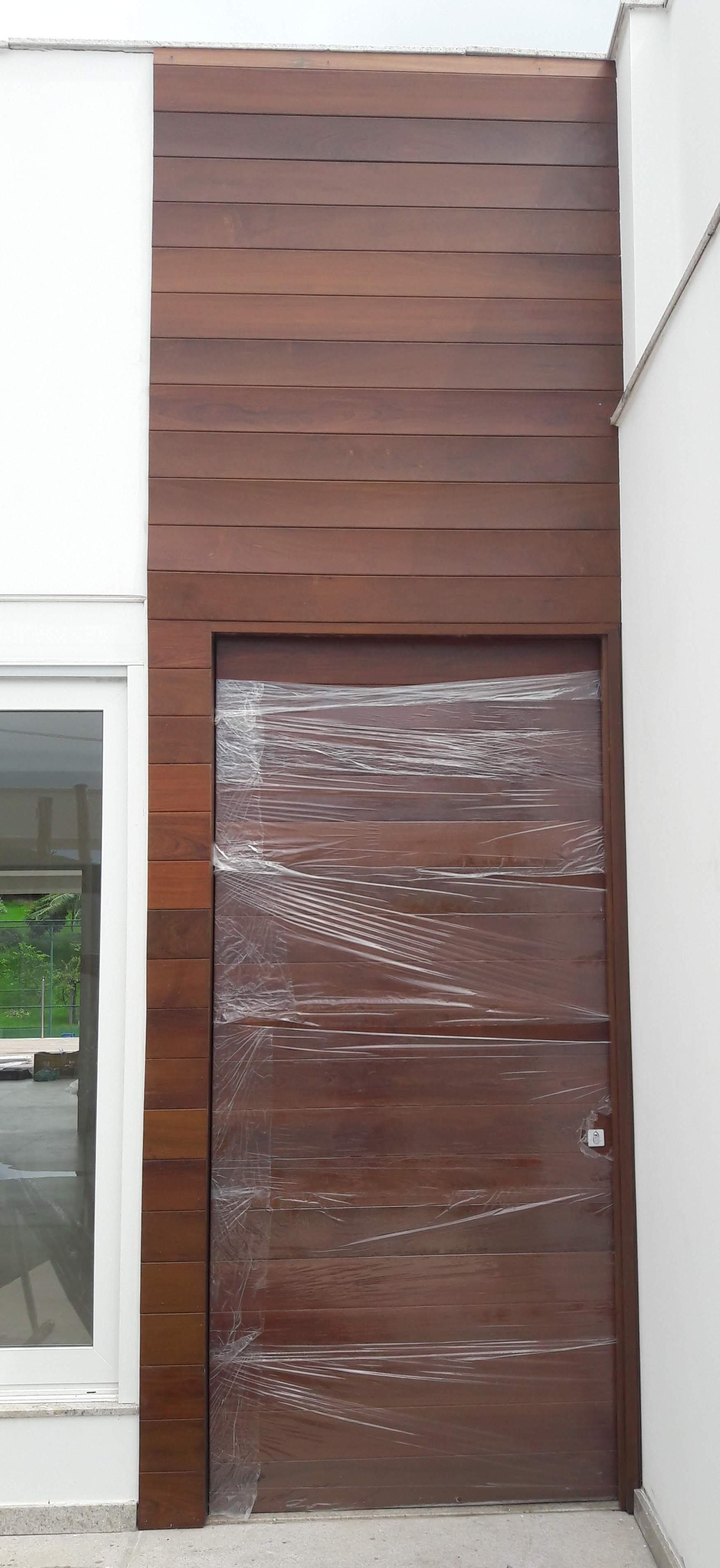 Porta de entrada em madeira, pivotante e painel em madeira.