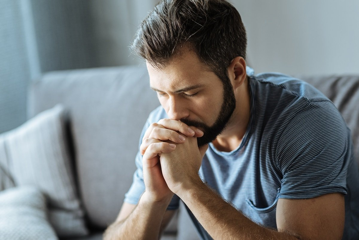 Stressed Out Man Sitting on Couch with Hands Folded and Eyes Closed