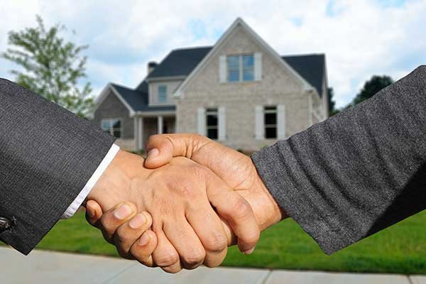 Real Estate Agent and Customers Shaking Hands Together