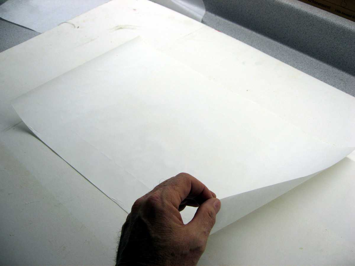 After applying the spray adhesive, stick the backing sheet to a piece of cardboard. Peel off the backing sheet. Repeat that process for 3 or 4 times. This will reduce the tack of the adhesive.