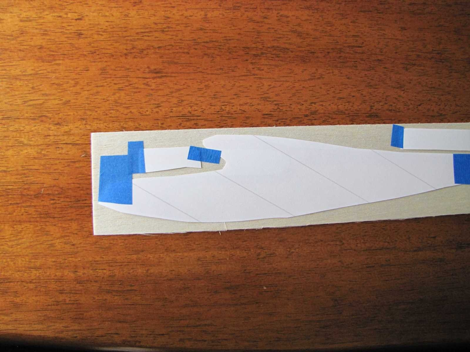 "Place the printed parts on your sheet of balsa. Any thickness balsa sheet can be used. The example shown is 1/32"" balsa sheet. Some tape may be useful in keeping them in position. It is important that the transfer paper not move while it is being ironed or the parts will blur."