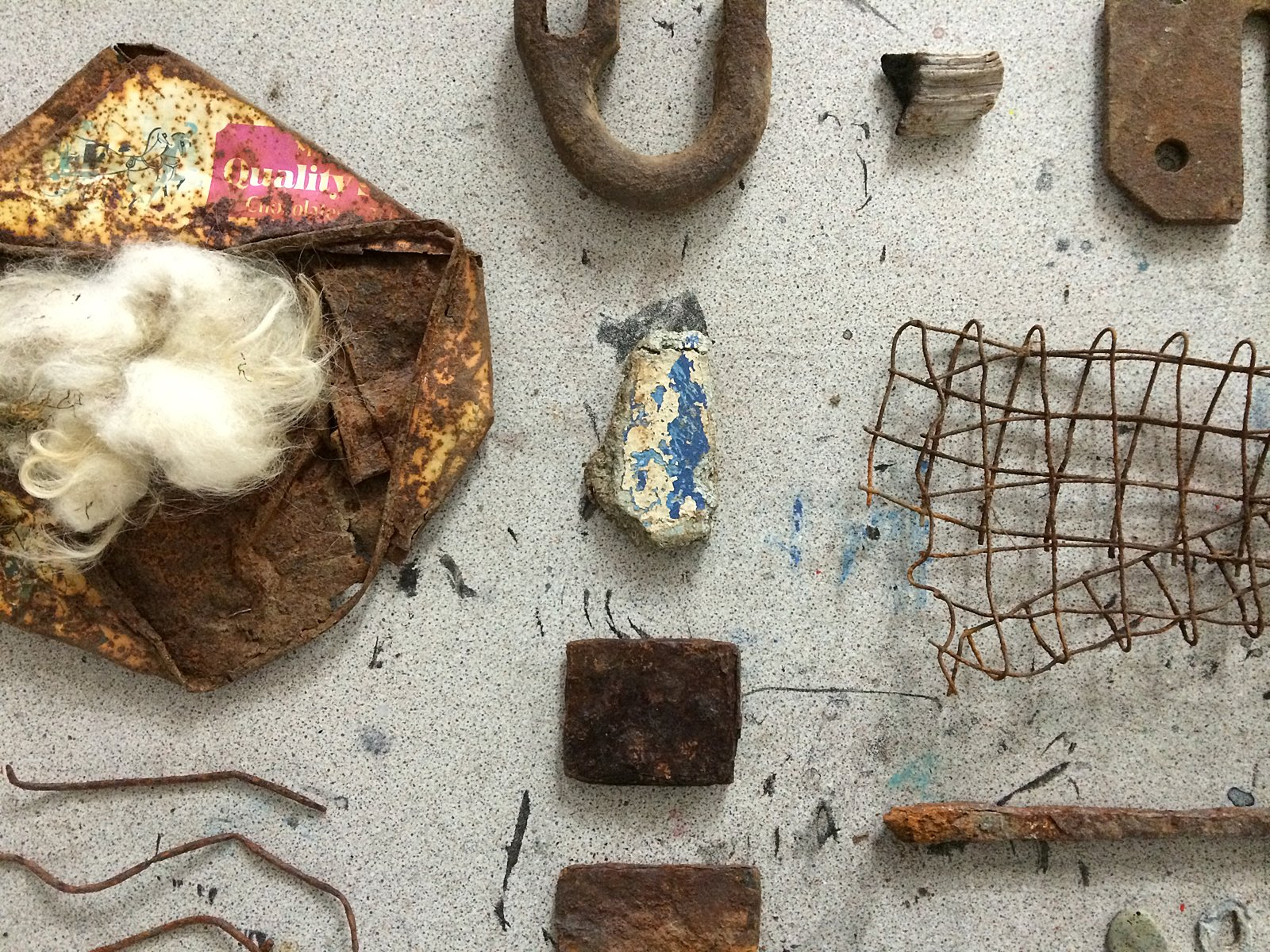 A closeup of rusted and other found objects placed on a grey speckled surface.