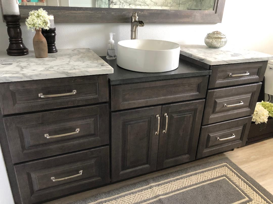 Featuring an elegant vanity with a single white vessel sink with satin nickel hardware.