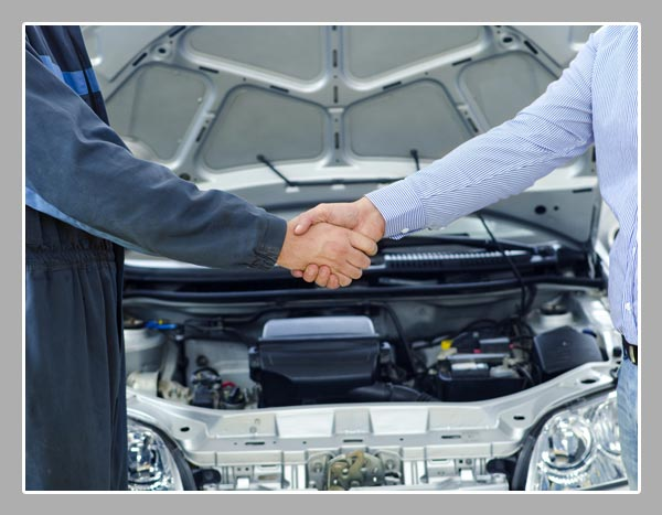 Mechanic and customer shaking hands