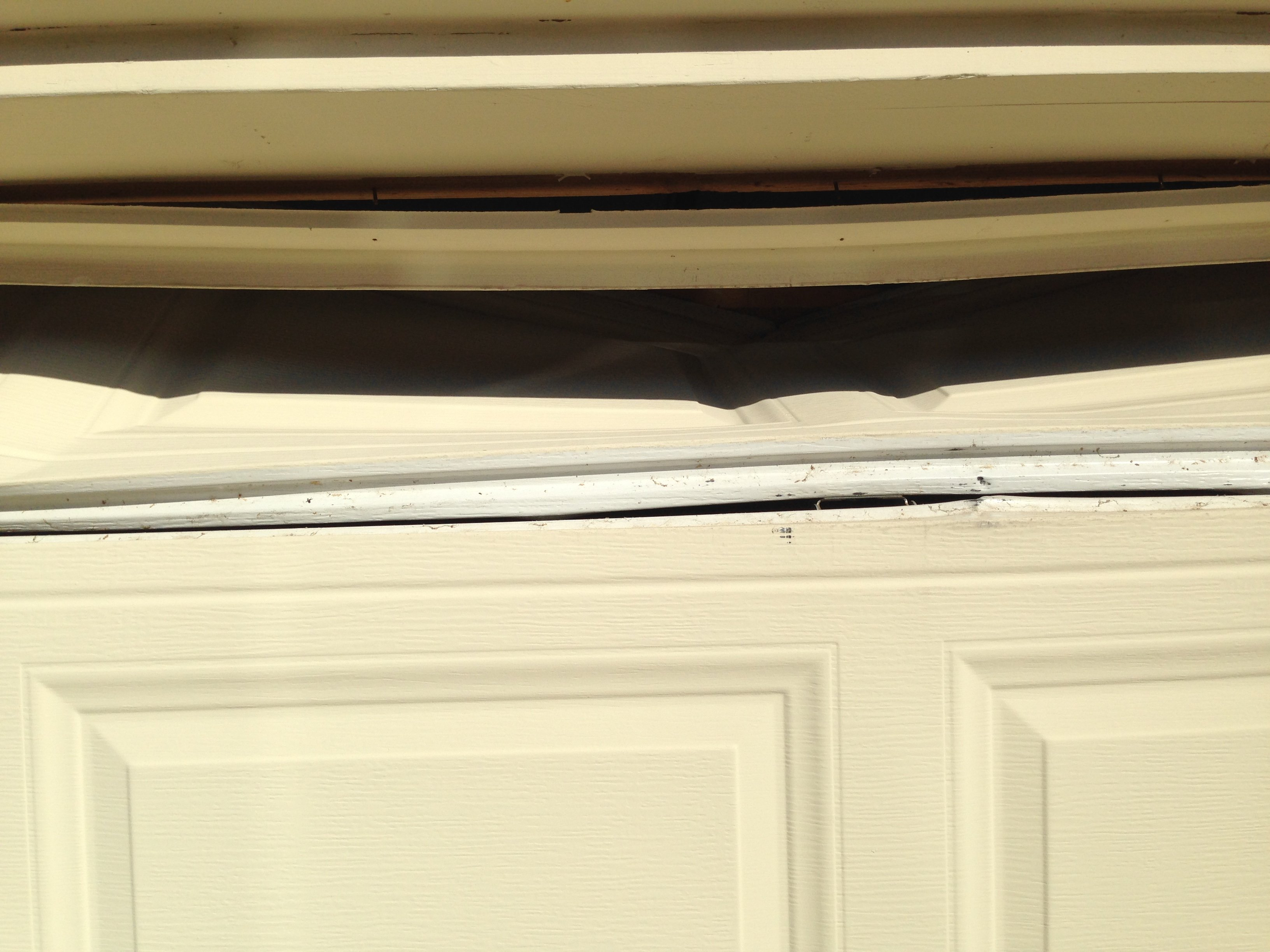 Hit by car backing out before door finished opening. Needs new section, support strut, and trim repair.