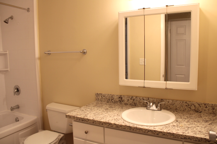 The bathroom has new, granite countertops and a new cabinet