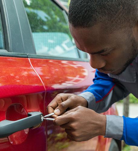 Mechanic Holding Lockpicker To Open Car Door